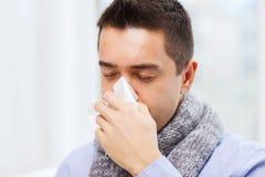 Закройте вверх больного человека с носом гриппа дуя дома Стоковые Изображения