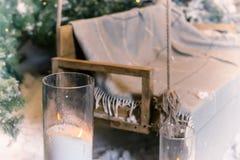 Закройте вверх больших свечей в стеклянных вазах близко отбросьте в снег-бухте Стоковые Изображения