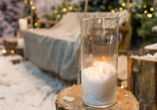 Закройте вверх больших свечей в стеклянных вазах в покрытом снег парке или Стоковое фото RF