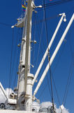 Закройте вверх большого крана доставки отличая лестницами водя к более высоким разделам на предпосылке голубого неба Стоковые Изображения