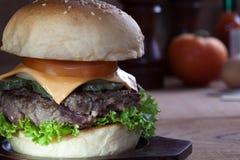 Закройте вверх бургера говядины с сыром на деревянной таблице Стоковое Фото