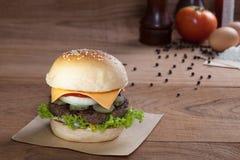 Закройте вверх бургера говядины с сыром на деревянной таблице Стоковые Фотографии RF