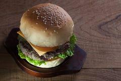 Закройте вверх бургера говядины с сыром на деревянной таблице Стоковое Изображение