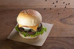 Закройте вверх бургера говядины с сыром на деревянной таблице Стоковые Изображения RF