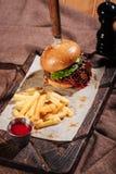 Закройте вверх бургера и фраев француза стоя на подносе Стоковое Изображение RF