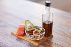 Закройте вверх бутылки еды и оливкового масла на таблице Стоковое Фото