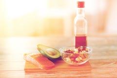 Закройте вверх бутылки еды и оливкового масла на таблице Стоковые Фото