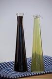Закройте вверх бутылки оливкового масла на салфетке Стоковые Изображения