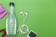 закройте вверх бутылки с водой, вахты и белых наушников на задней части зеленого цвета Стоковое фото RF