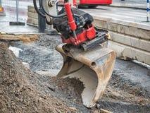 Закройте вверх ведра экскаватора, грейдера или трактора, реновации дороги города на предпосылке стоковые фотографии rf