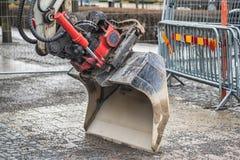 Закройте вверх ведра экскаватора, грейдера или трактора, реновации дороги города на предпосылке стоковые изображения rf