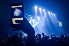 Закройте вверх видео записи с smartphone во время концерта Толпа на концерте и запачканных светах этапа стоковое фото