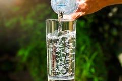 Закройте вверх воды пропуская от бутылки питьевой воды в стекло на запачканной зеленой предпосылке сада Стоковое Изображение