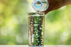 Закройте вверх воды пропуская от бутылки питьевой воды в стекло на запачканной зеленой предпосылке bokeh Стоковые Изображения