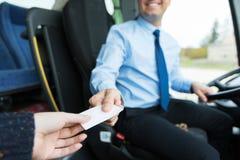 Закройте вверх водителя автобуса продавая билет к пассажиру стоковые фото