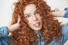 Закройте вверх волос красивой девушки имбиря касающих усмехаясь показывающ язык смотря камеру Белая предпосылка Стоковое Фото