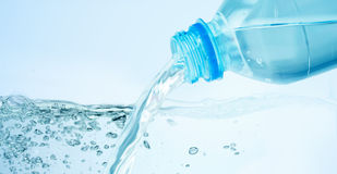 Закройте вверх воды лить от пластичной бутылки стоковое изображение