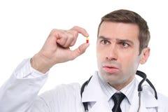 Закройте вверх вспугнутого врача смотря желт-красную пилюльку Стоковые Фотографии RF