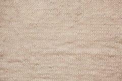 Закройте вверх вязать бежевую текстурированную предпосылку шерстей, винтажный старый стиль Стоковое Изображение RF