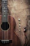 Закройте вверх гавайской гитары и наушника на старой деревянной предпосылке Стоковые Фотографии RF
