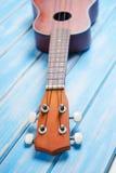 Закройте вверх гавайской гитары на голубое деревянном Стоковая Фотография