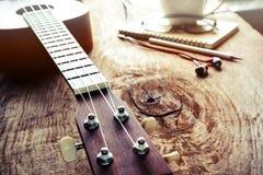 Закройте вверх гавайской гитары на старой деревянной предпосылке с мягким светом Стоковые Изображения