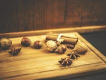Закройте вверх гаек и циннамона на деревянной предпосылке Стоковые Изображения