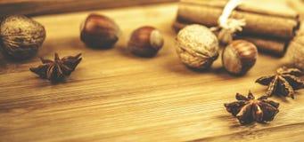 Закройте вверх гаек и циннамона на деревянной предпосылке Стоковые Фотографии RF
