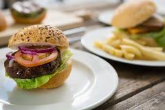 Закройте вверх гамбургера в плите на таблице Стоковое Изображение