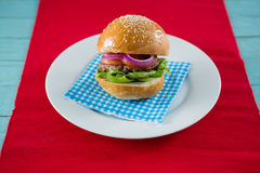 Закройте вверх гамбургера, который служат на салфетке в плите Стоковое Изображение