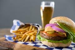 Закройте вверх гамбургера, который служат с французскими фраями и пивом Стоковая Фотография