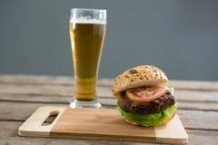 Закройте вверх гамбургера на разделочной доске пивом Стоковое Изображение RF