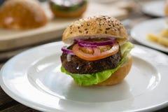 Закройте вверх гамбургера с овощами в плите Стоковая Фотография
