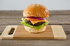 Закройте вверх гамбургера с сыром на разделочной доске Стоковое Изображение