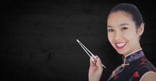 Закройте вверх гейши с палочками против темной деревянной панели Стоковая Фотография RF
