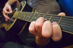 Закройте вверх гитариста играя акустическую гитару Стоковое Изображение