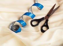 Закройте вверх голубой переплетенной рулетки и ножниц на cream ткани с волнистостью стоковая фотография rf