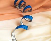 Закройте вверх голубой переплетенной рулетки на сливк и бежевой ткани стоковое изображение