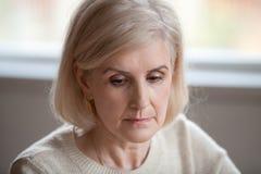 Закройте вверх грустной старшей женщины вспоминая пропускающ прошлый стоковое изображение