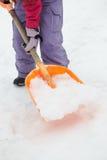 Закройте вверх девочка-подростка копая снежок от путя Стоковые Фото