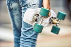 Закройте вверх девушки или мальчика держа его скейтборд пенни Стоковые Изображения