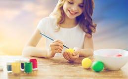 Закройте вверх девушки крася пасхальные яйца Стоковая Фотография