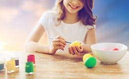Закройте вверх девушки крася пасхальные яйца Стоковые Фото