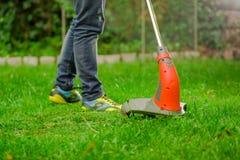 Закройте вверх джинсов молодого работника нося и использования травы вырезывания косилки триммера лужайки в запачканной предпосыл Стоковое фото RF