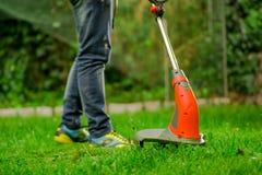 Закройте вверх джинсов молодого работника нося и использования травы вырезывания косилки триммера лужайки в запачканной предпосыл Стоковые Фотографии RF