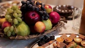 Закройте вверх для традиционной таблицы с яблоками, виноградинами, грушами и различными восточными помадками с гайками, едой и акции видеоматериалы