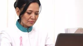 Закройте вверх доктора розовой осведомленности рака ленты женского работая на клинике стоковое изображение