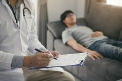 Закройте вверх доктора ручки писать с пришл навестить пациент дома пока он страдал от язв желудка и заметило tre стоковые изображения