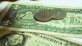 Закройте вверх долларовых банкнот и монеток на белой предпосылке