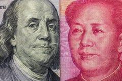 Закройте вверх 100 долларов и 100 банкнот Yaun с фокусом на портретах Бенджамина Франклина и Мао Дзе Дуна /USA против Китая t стоковое изображение rf